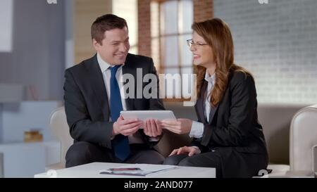 Excited business partners laughing, holding tablet with online startup project - Stock Photo