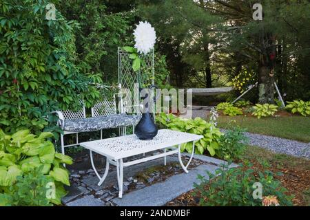 White wrought iron metal table and sitting bench furniture  on slabs of grey granite and bordered by Hosta plants in backyard country garden in summer - Stock Photo