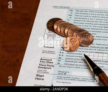 1040 individual income tax return form 2019 with pen and pennies. Concept of filing taxes, payment, refund, and April 15, 2020 deadline date - Stock Photo