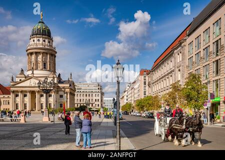 22 September 2018: Berlin, Germany - Horse-drawn carriage ride in Gendarmenmarkt Square, with the French Church on the left, tourists watching as it g - Stock Photo