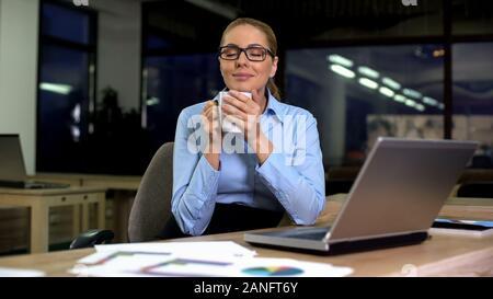 Happy businesswoman enjoying fragrant aroma of coffee, having break from work - Stock Photo