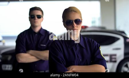 Female and male police officers with crossed hands looking into camera, security - Stock Photo