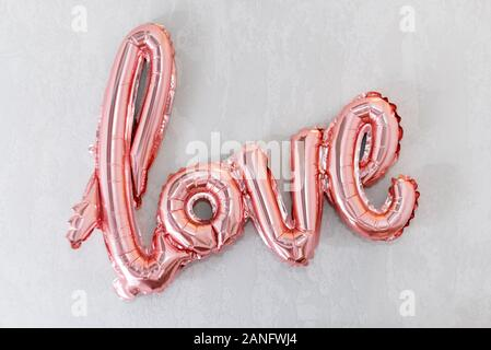 Love word from pink inflatable balloon on grey concrete background. The concept of romance, Valentine's Day. Love rose gold foil balloon - Stock Photo