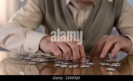 Male pensioner assembling jigsaw puzzle at home, alzheimer rehabilitation, hobby