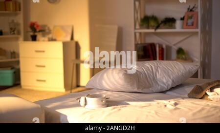 White alarm clock lying on messy bed, crumpled bed sheets, oversleeping concept - Stock Photo