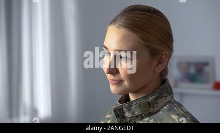Happy female soldier in camouflage uniform watching military march in window - Stock Photo