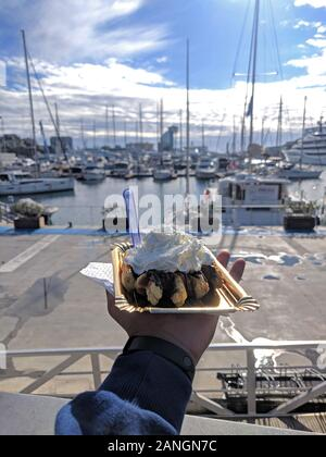 Man holding Belgian Waffle in hand with whipped cream with marina backdrop - Stock Photo