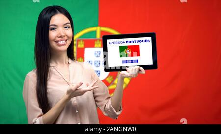 Lady holding tablet with learn Portuguese app, flag on background, education - Stock Photo