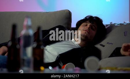 Drunk man sleeping on sofa after party at home, empty bottles on table, addict - Stock Photo