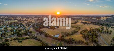Sun touching the horizon at sunset over Australian outback - wide aerial panorama - Stock Photo