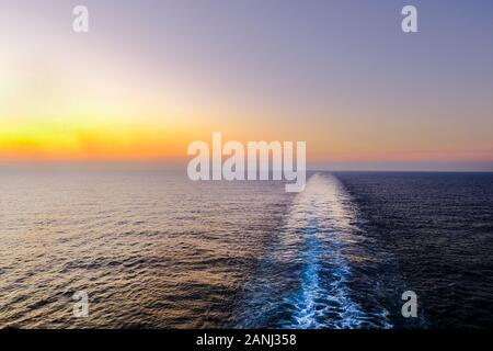 A shot of the ships wake taken from the rear or stern of a ship as it sales across the sea at sunset. - Stock Photo
