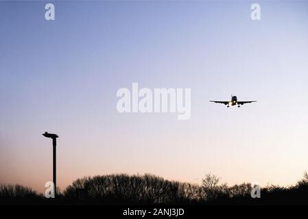 A low flying plane approached Heathrow airport, London, LHR, in the morning from an easterly direction. The plane has its landing gear down. - Stock Photo