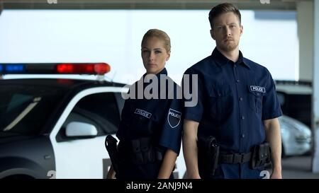 Confident woman and man police officers standing near patrol car, on duty - Stock Photo