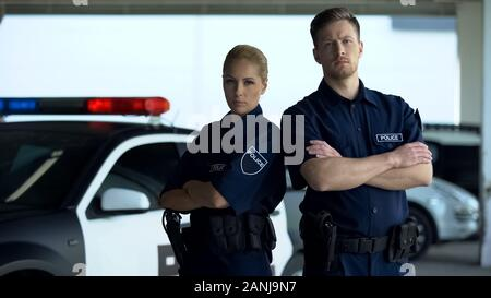 Confident man and woman police officers standing near patrol car crossing hands - Stock Photo
