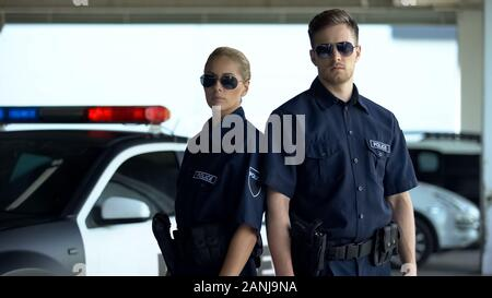 Confident policewoman and man in sunglasses standing near patrol car, on duty - Stock Photo