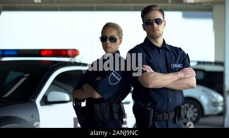Brave policewoman and man in sunglasses standing with folded hands near car - Stock Photo