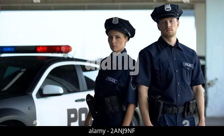 Two serious policemen in uniform and service cap posing near patrol car, order - Stock Photo