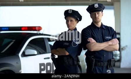 Two brave policemen in uniform and service cap posing near patrol car, order - Stock Photo