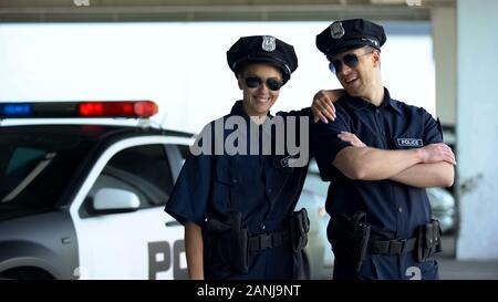 Friendly police officers in uniform and glasses smiling to camera, law and order - Stock Photo