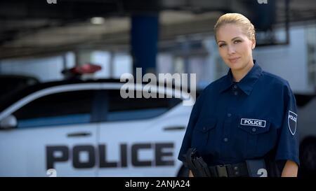 Female police officer smiling, standing near patrol car, maintenance of order - Stock Photo