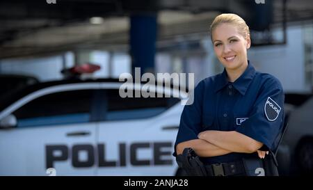 Woman police officer smiling, standing near patrol car with crossed hands, law - Stock Photo