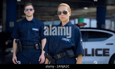Serious woman and man police officers in sunglasses standing outdoor, safety - Stock Photo