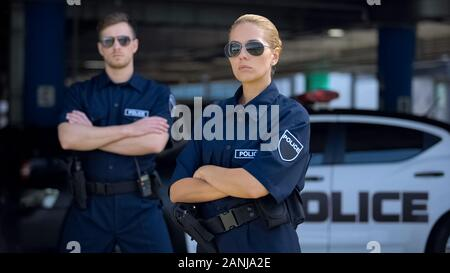 Serious man and woman police officers in sunglasses standing outdoor, safety - Stock Photo