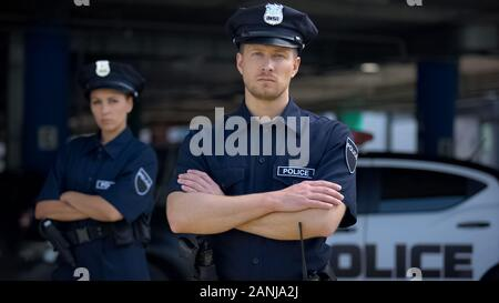 Confident male and female police officers in uniform standing near patrol car - Stock Photo
