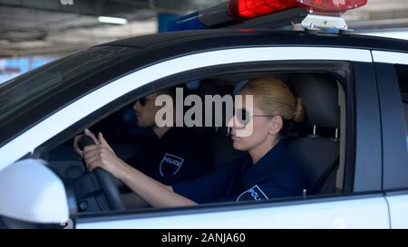 Female and male police officers wearing sunglasses sitting in patrol car, law - Stock Photo