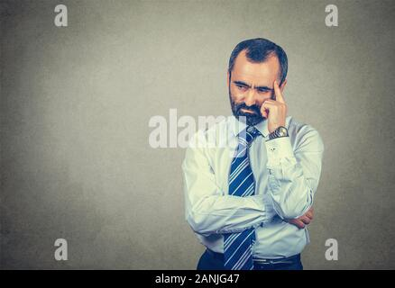 Closeup portrait bearded adult man having stressful thoughts, thinking, having migraine pain headache. Mixed race bearded model isolated on gray studi - Stock Photo