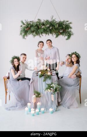 Wedding party at dinner - Bridal couple with bridesmaids and groommen drinking champagne and have fun at the decorated wedding table - Stock Photo