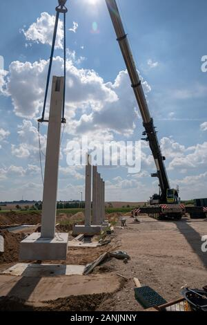 on a construction site, concrete columns for a factory building are placed with the help of a large crane - Stock Photo