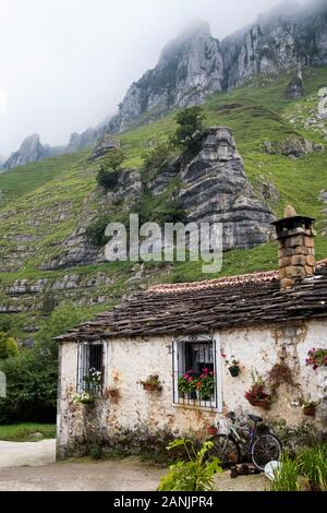 Traditional stone house at the foot of limestone outcrops in Valle del Miera valley (San Roque de Riomiera, Valles Pasiegos, Cantabria, Spain) - Stock Photo