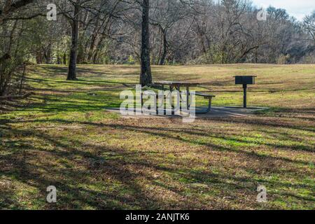 An empty picnic table and grill under the shaded trees on a cement pad surrounded by trees and grass in a park in the forest on a bright sunny day in - Stock Photo