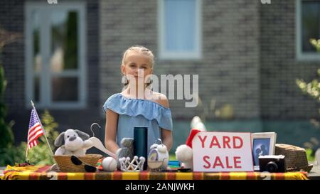 Young business lady selling old toys on yard sale, earning extra pocket money - Stock Photo