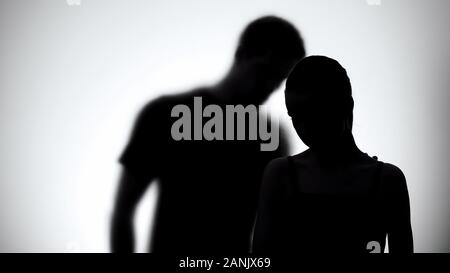 Silhouettes of upset woman and man together, experiencing life difficulties - Stock Photo
