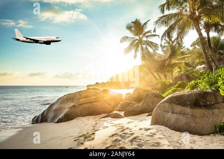 Airplane Is Flying In Cloudy Sky Over Island And Sea In Summer At Seychelles - Stock Photo