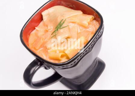 Homemade tomato soup made with rainbow bow tie pasta and served in a black coffee cup. Isolated on white background. - Stock Photo