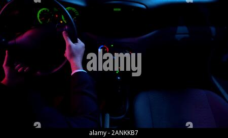Man driving auto at night alone, round-the-clock taxi service, car interior - Stock Photo