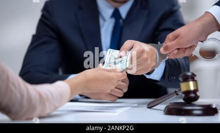 Corrupt judge handcuffed when taking dollar bribe in court, anti-corruption law - Stock Photo