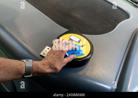 London England - August 15 2019; Using London's Oyster Card on reader when gtting on bus. - Stock Photo