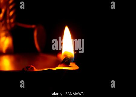 Close view of lit diya lamp against dark background. Lamp made out of silver metal lit during festival. - Stock Photo