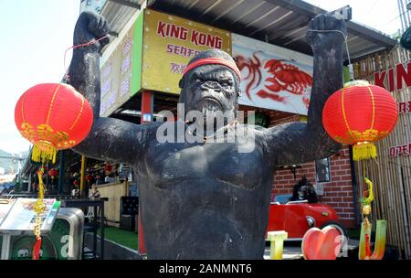 The King Kong Seafood restaurant in Patong Beach, Phuket, Thailand, Asia, has put Chinese New Year decorations on its figure of King Kong in front of the restaurant. The New Year, or Spring Festival, begins on January 25 and ends on February 4. 2020 is the year of the rat. - Stock Photo