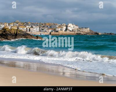 The seaside town of St. Ives a seen over the waves and sea surf  of sandy Porthminster Beach, Cornwall, England, UK. - Stock Photo
