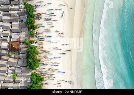 View from above, stunning aerial view of a fishing village with houses and boats on a white sand beach bathed by a beautiful turquoise sea. - Stock Photo