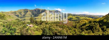Panoramic view over a forest with a little hut embedded and green mountains, sunny day, Drakensberg, Giants Castle Game Reserve, South Africa - Stock Photo