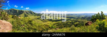 Panorama of a some mountains and a green and vast valley on a sunny day, Drakensberg, Giants Castle Game Reserve, South Africa - Stock Photo