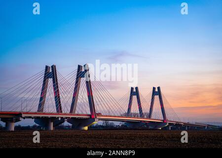 Monumental, lighted, new modern double cable-stayed bridge over Vistula River in Krakow, Poland during sunset. - Stock Photo