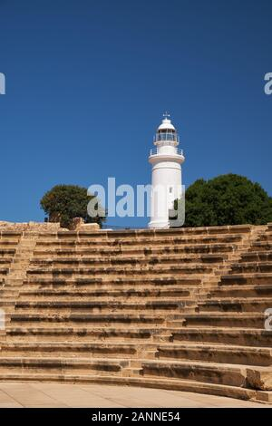 The view of seats rows of Odeon with lighthouse on the background in the Paphos Archaeological Park. Cyprus - Stock Photo