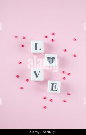 Love message written in white wooden blocks on pink background. Pink candy hearts. Flat lay, top view - Stock Photo